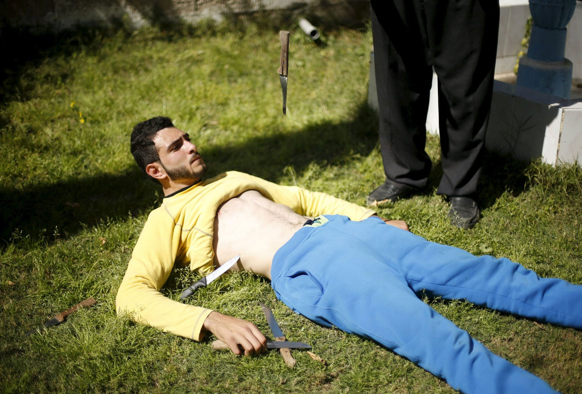 Palestinian Mohammad Baraka, 20, nicknamed by people as Gaza Samson, has knives dropped on his stomach as he exercises in Deir al-Balah in the central Gaza Strip March 5, 2016.
