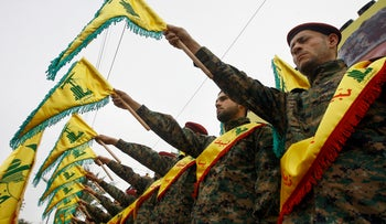 Hezbollah fighters hold flags as they attend the funeral procession of a Hezbollah senior commander killed in Syria, March 2, 2016.
