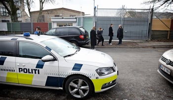 Headmaster Jan G. Hansen, right, talks to the press as police are seen in front of the Jewish school that a 16-year-old Danish girl is accused of plotting to attack. March 8. 2016.