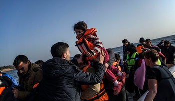 A Syrian man helps a girl to disembark from a dinghy used by refugees and migrants to arrive to Mytilene, Lesbos, February 29, 2016.