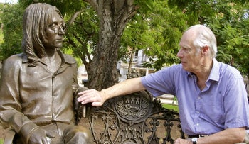In this Oct. 30, 2002 file photo, Beatles producer George Martin touches a statue of John Lennon in a park in the Vedado neighborhood of Havana, during his visit to Cuba.