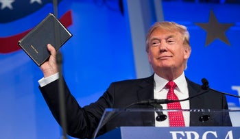 Donald Trump, a 2016 Republican presidential candidate, holds up a Bible while speaking at the Values Voter Summit in Washington, D.C., U.S., on Friday, Sept. 25, 2015.