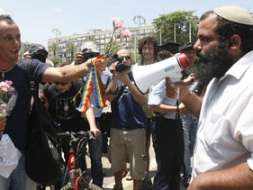 A gay pride parade participant hands flowers to a right-wing activist in Rabin Square, Tel Aviv, June 8, 2007.