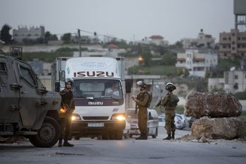 Israeli soldiers check Palestinians at a checkpoint on the road to the village of Hajja near the West Bank city of Nablus, Wednesday, March 9, 2016.