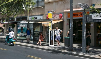 A Tel Aviv bus stop with a solar-powered sign at right, 2015