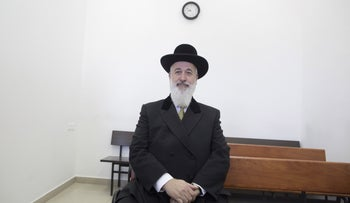 Former Chief Rabbi Yona Metzger, sitting on the bench,  at the opening of his trial on bribery charges.