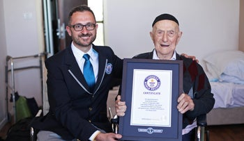In this photo supplied by the Guinness World Records, Marco Frigatti, Head of Records for Guinness World Records, presents Israel Kristal a certificate for being the oldest living man, in Haifa, Israel, March 11, 2016.