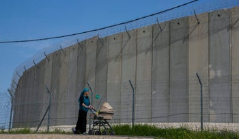 Israeli settler walks with a stroller past the West Bank separation barrier near Abu Dis.