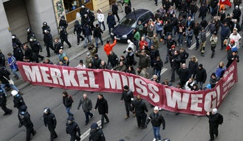 Far right-wing supporters march during a rally against the German government's immigration policies holding a slogan reading 'Merkel must go,' Berlin, Germany, March 12, 2016.