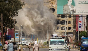 Smoke billows after a mortar shell hit a building during clashes between forces loyal to Yemen's Saudi-backed president and Huthi rebels, Taiz, Yemen, March 12, 2016.