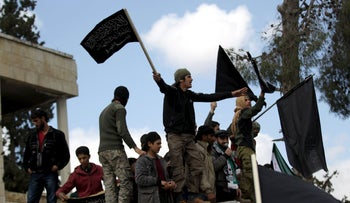 Protesters carry Nusra Front flags during an anti-government protest in Marat Numan in Idlib province, northwestern Syria, March 11, 2016.