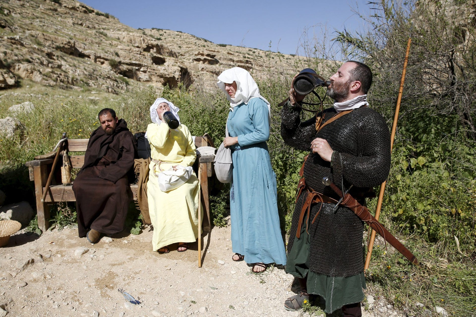 History enthusiasts dressed in costumes rest after a march during an event to relive the experiences of pilgrims who travelled to Jerusalem during medieval times, at a historical fortress near the settlement of Ma'ale Adumim in the West Bank, east of Jerusalem, March 11, 2016.