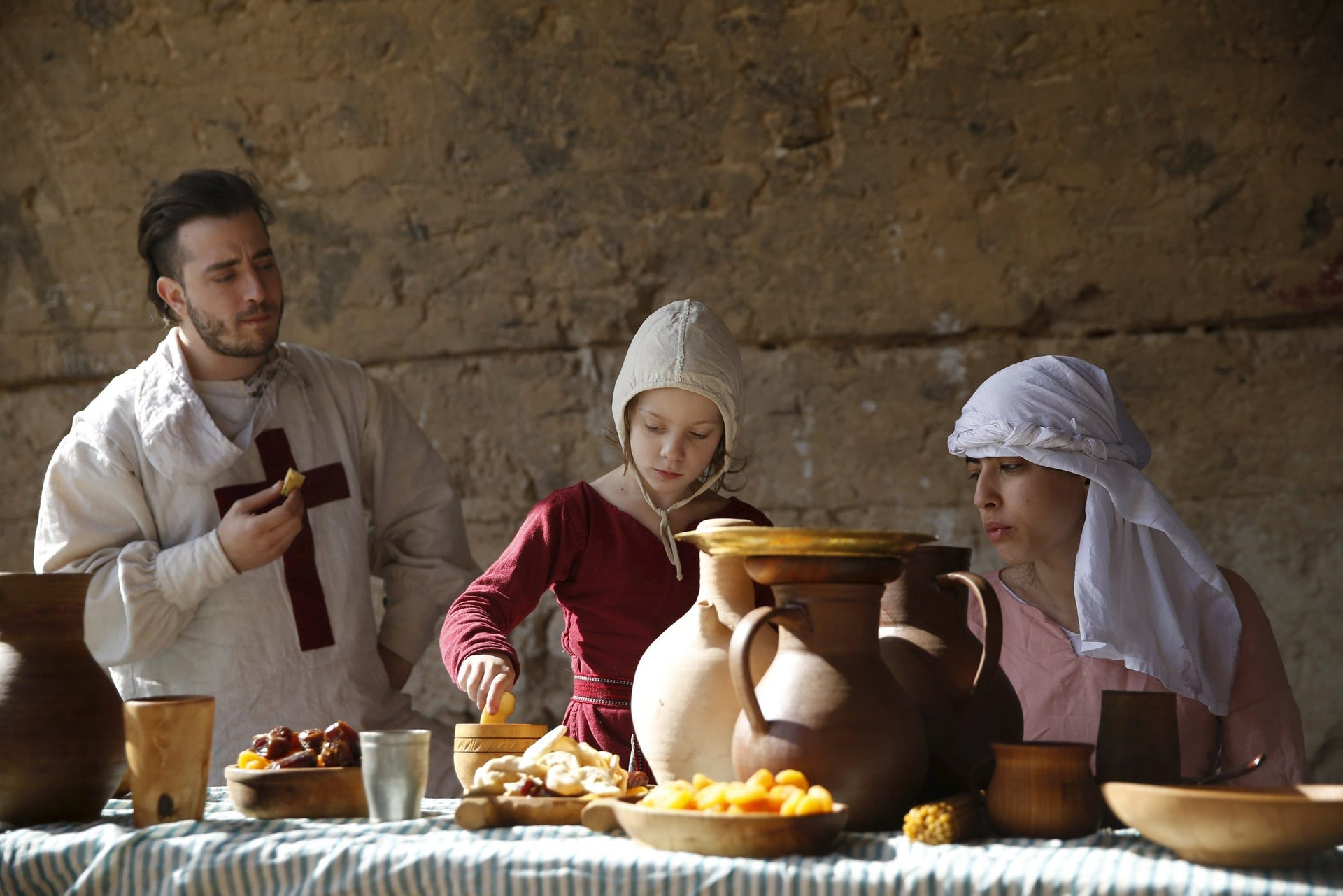 History enthusiasts dressed in costumes sit next to a table during an event to relive the experiences of pilgrims who travelled to Jerusalem during medieval times, at a historical fortress near the settlement of Ma'ale Adumim in the West Bank, east of Jerusalem, March 11, 2016.