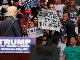 "Republican presidential candidate Donald Trump, left, looks on as a Trump supporter reaches for a sign that reads ""Islamophobia is not the answer"" at a rally in Oklahoma City, Friday, Feb. 26, 2016."