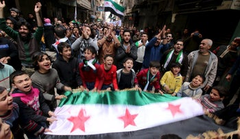 Protesters shout slogans and carry Free Syrian Army flags during an anti-government protest in Aleppo, Syria, on March 11, 2016.