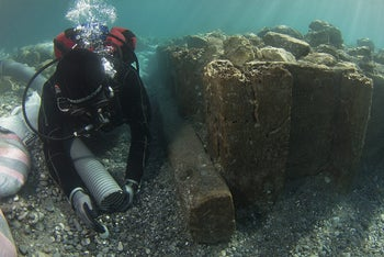 An archaeologist documenting a wooden caisson found during the underwater excavation of the Corinthian port of Lechaion, Greece.