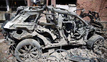 A Yemeni man stands next to a damaged vehicle after an airstrike by Saudi-led coalition in Sanaa, Yemen, Saturday, Feb. 27, 2016.