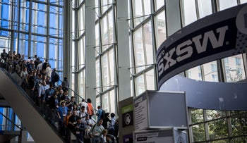 Attendees ride on escalators inside the Austin Convention Center during the South By Southwest (SXSW) Interactive Festival in Austin, Texas, March 12, 2016.