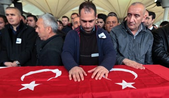 People stand by the Turkish flag-draped coffin of a man killed at Sunday's explosion during a funeral procession in Ankara, Turkey, March 14, 2016.