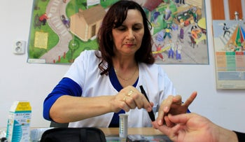 A diabetes educator performs a blood sugar test