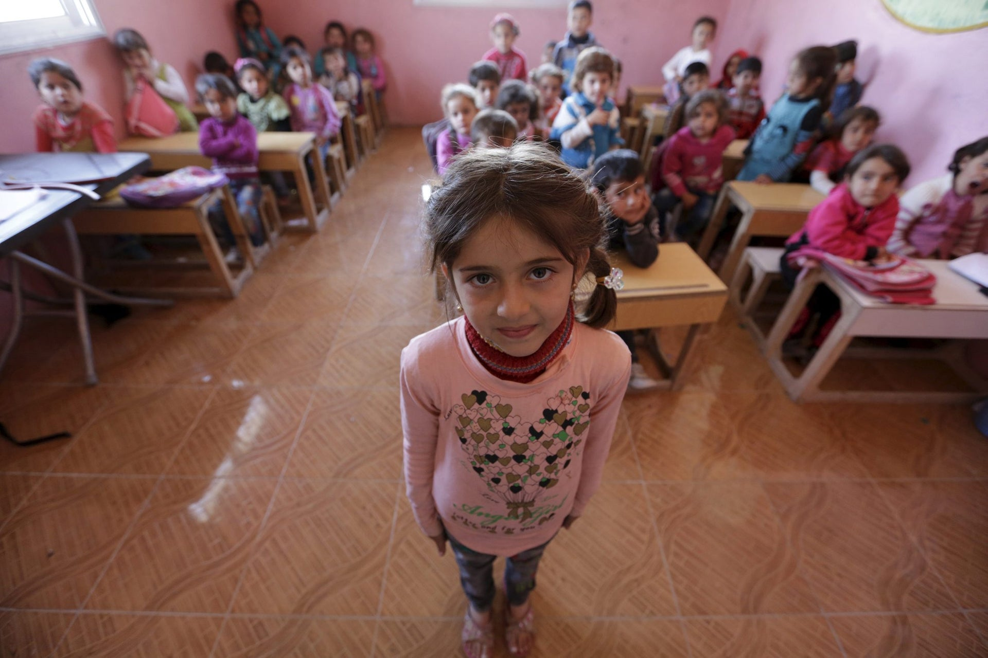 Five-year-old Razan Nader poses inside a classroom in the rebel-controlled area of Maarshureen village in Idlib province, Syria March 12, 2016.