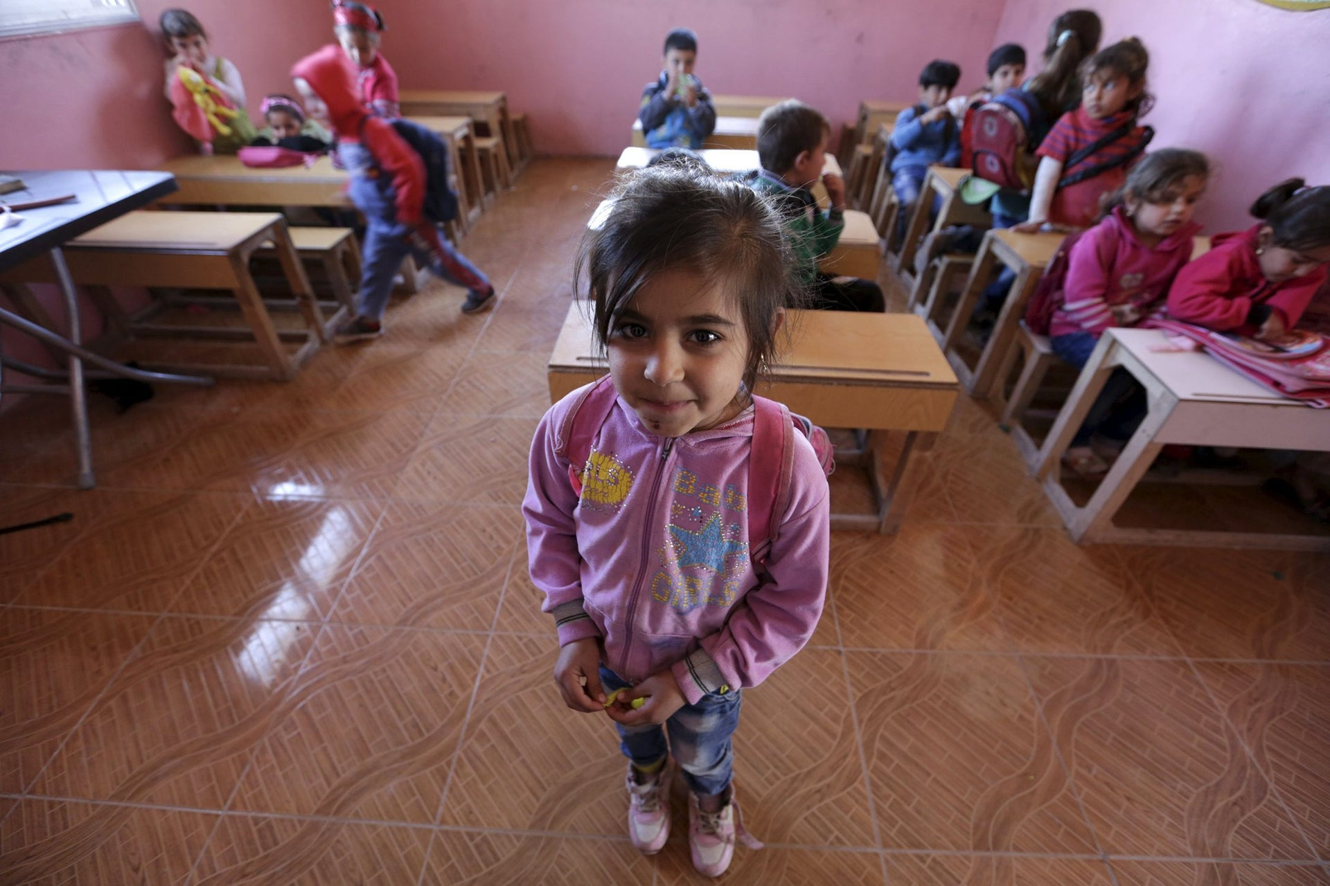 Five-year-old Sandas al-Mohamed poses inside a classroom in the rebel-controlled area of Maarshureen village in Idlib province, Syria March 12, 2016.
