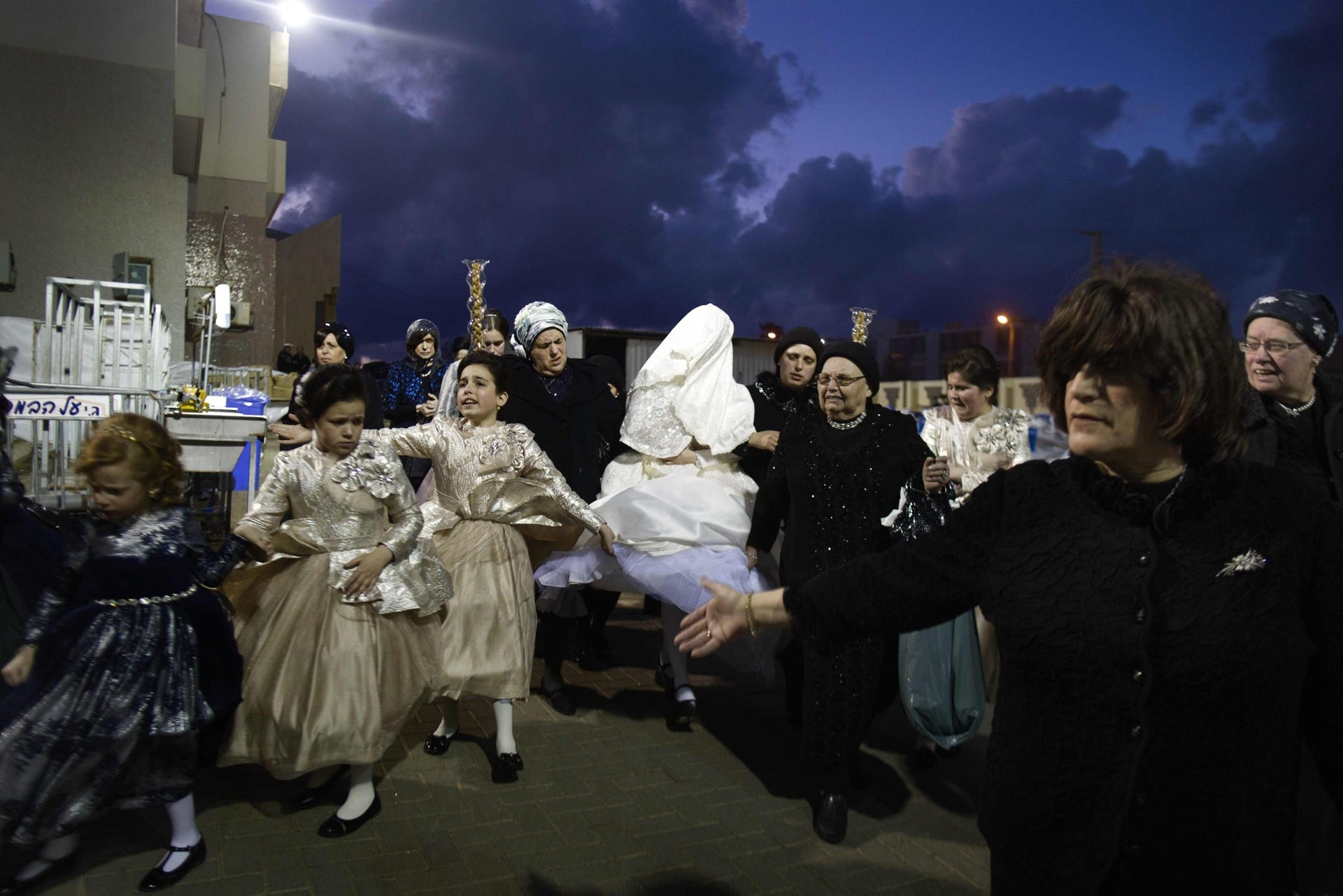 Family members lead Ultra-Orthodox Jewish bride Parowol Mirel Lamber, from the Toldos Avrohom Yitzchok (Hasidic dynasty), to marry the great-grandson of the Rabbi of the Tzanz Ultra-Orthodox Hasidic community at a wedding ceremony on March 15, 2016, in the Israeli central city of Netanya.