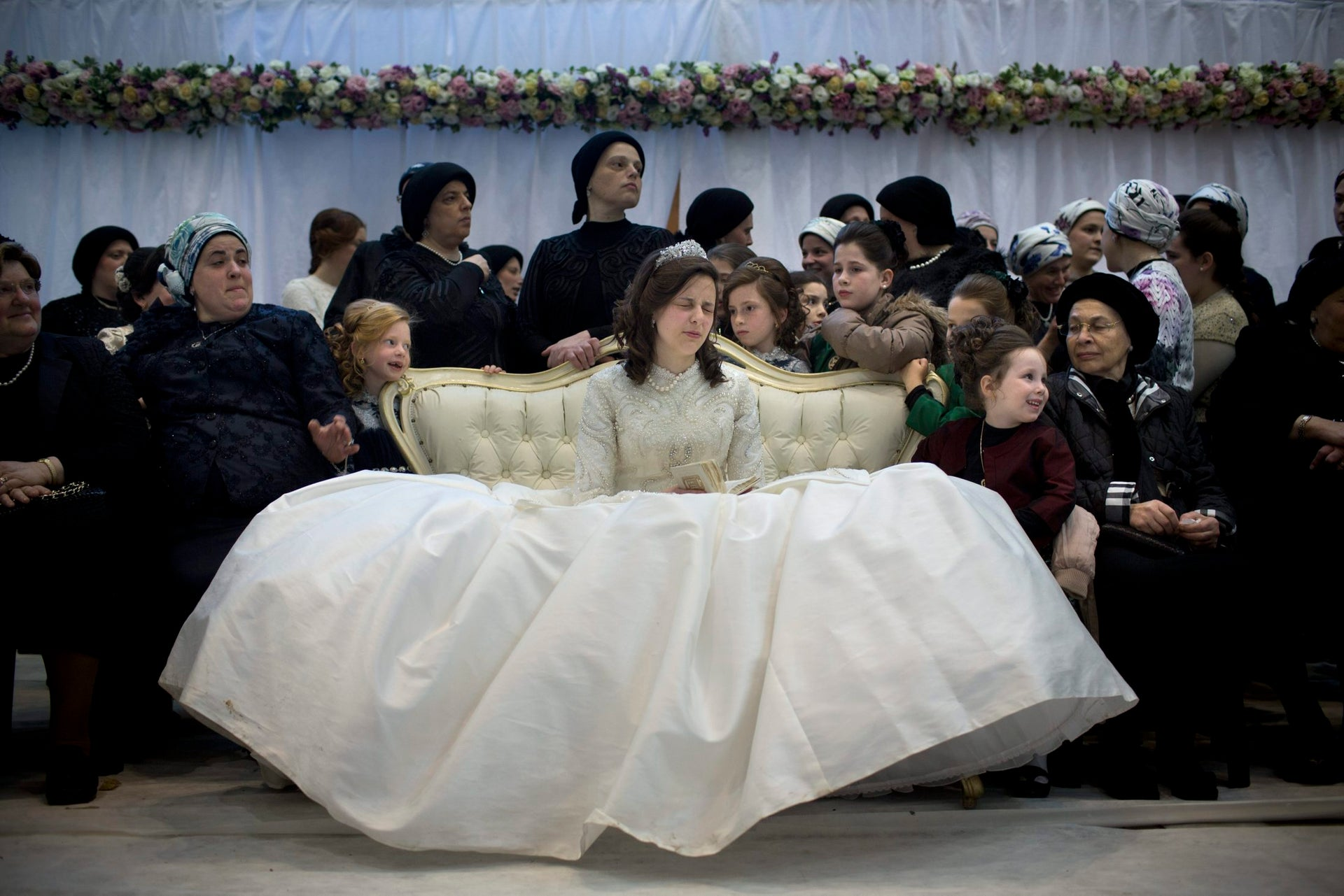 A Jewish bride sits with family members in the women's section during her wedding to the grandson of the Rabbi of the Tzanz Hasidic dynasty community, in Netanya, Israel, Tuesday, March 15, 2016.
