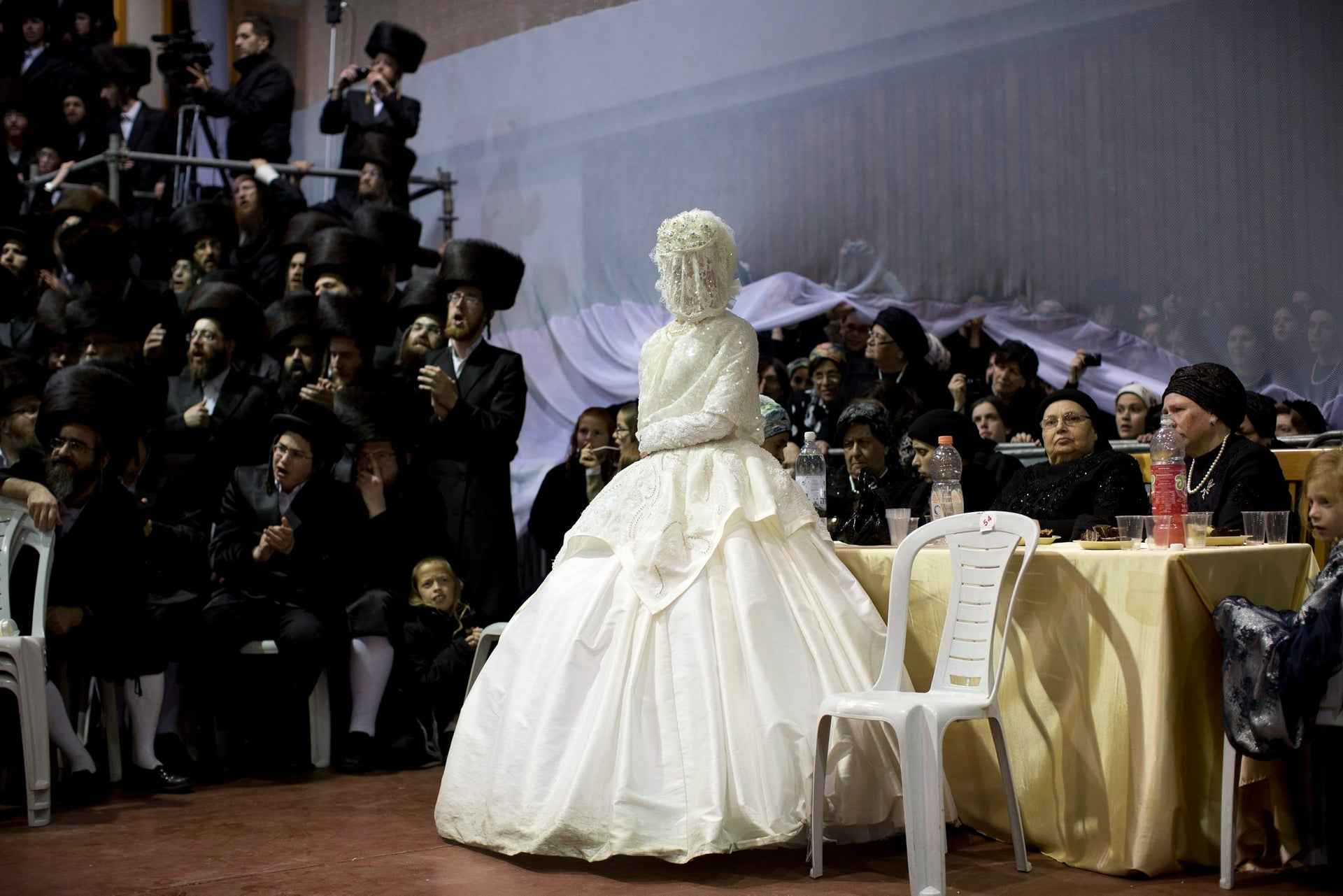 An ultra-Orthodox Jewish bride enters to the men's section of the wedding, to fulfill the Mitzvah tantz, in which family members and honored rabbis are invited to dance in front of the bride, often holding a gartel, and then dancing with the groom, during her wedding to the grandson of the Rabbi of the Tzanz Hasidic dynasty community, in Netanya, Israel,in Netanya, Israel, Wednesday, March 16, 2016.