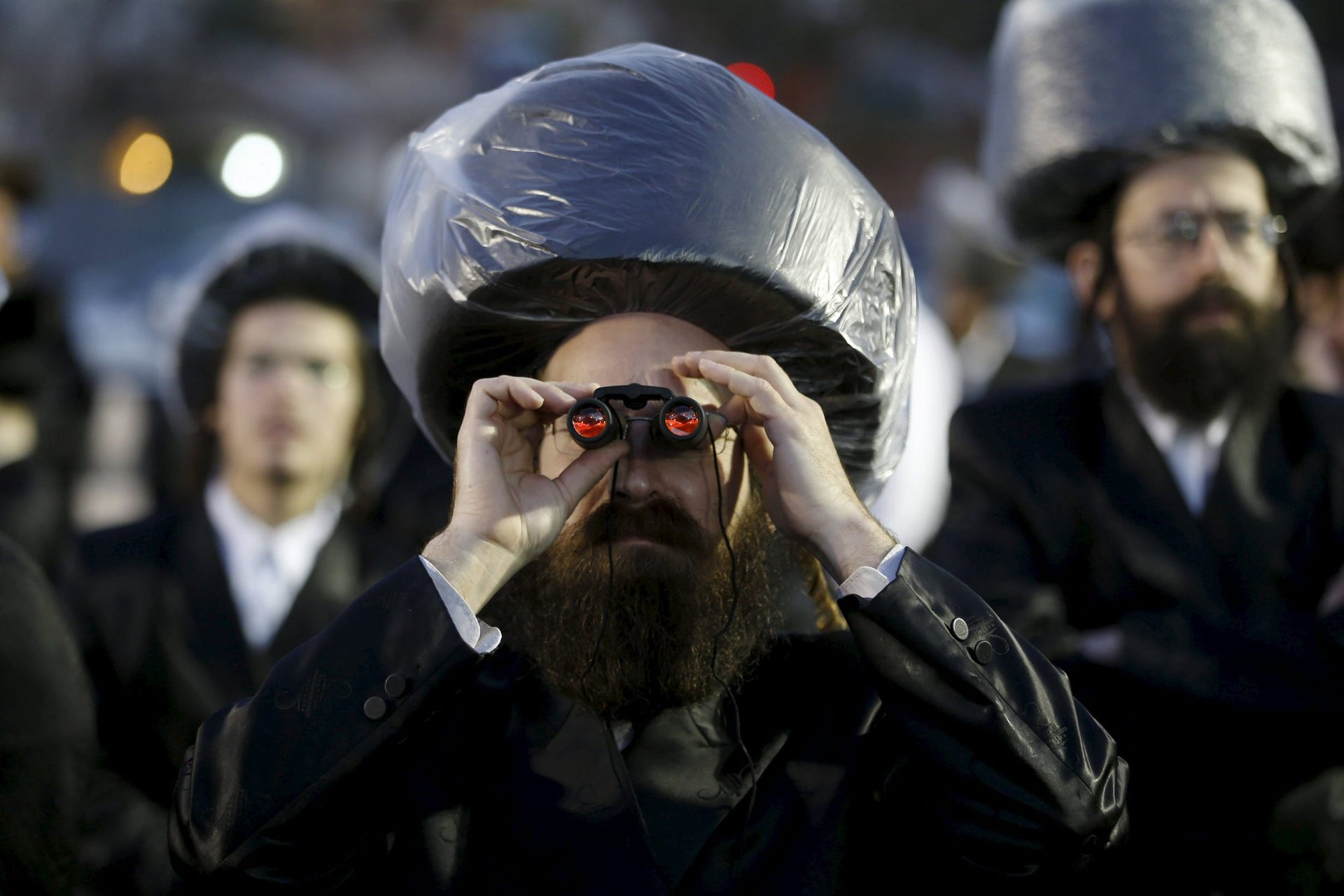 An ultra-Orthodox Jewish man uses binoculars during the wedding ceremony the grandson of Rabbi Yosef Dov Moshe Halberstam, religious leader of the Sanz Hasidic dynasty and the granddaughter of the religious leader of Toldos Avraham Yitzchak Hasidic dynasty, in Netanya, Israel March 15, 2016.