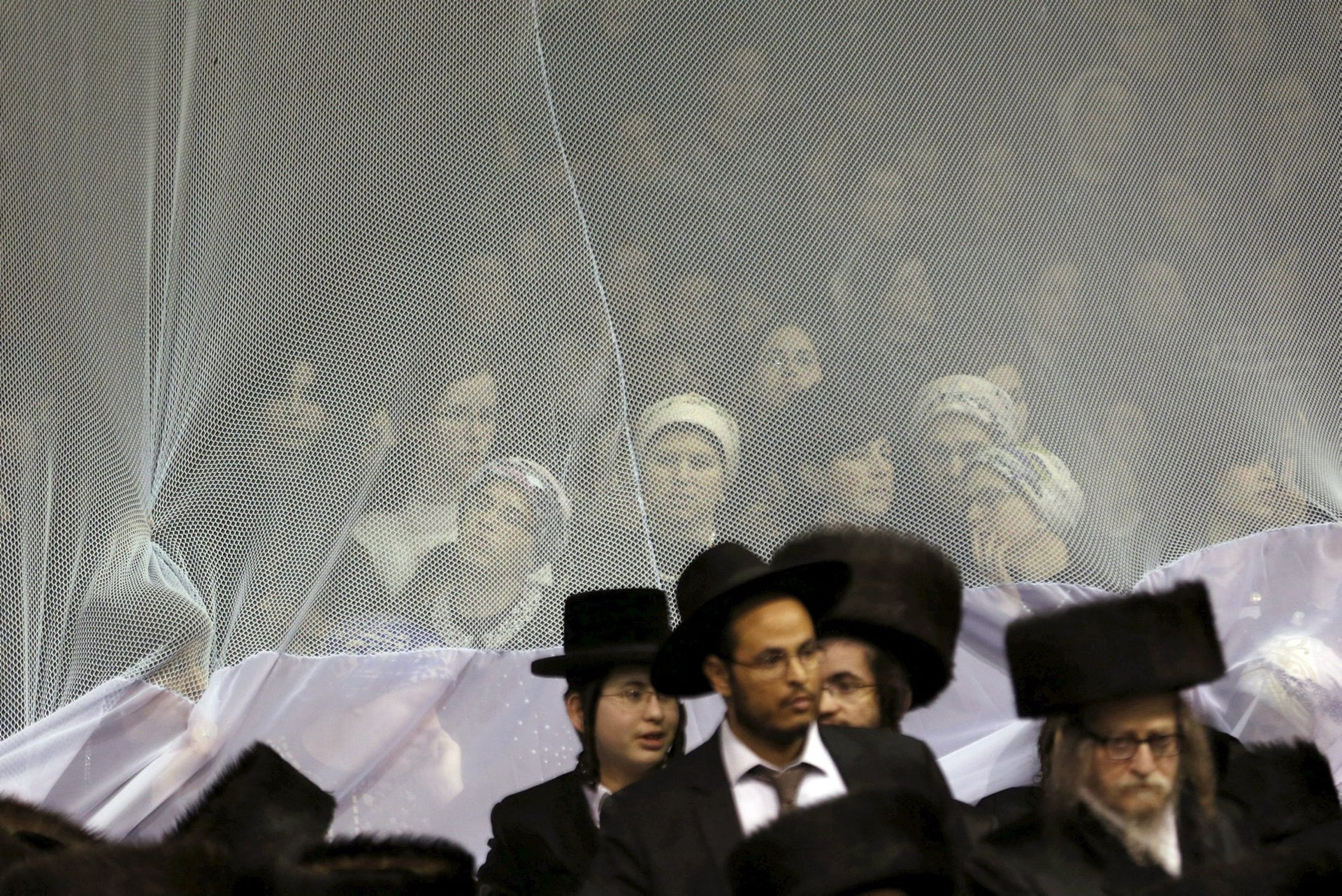 Ultra-Orthodox Jewish men and women attend the wedding ceremony of the grandson of Rabbi Yosef Dov Moshe Halberstam, religious leader of the Sanz Hasidic dynasty, and the granddaughter of the religious leader of Toldos Avraham Yitzchak Hasidic dynasty, in Netanya, Israel, early March 16, 2016.