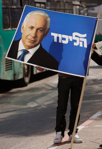 """A supporter holds an election billboard showing Israel's Likud Party leader Benjamin Netanyahu with Hebrew writing that reads """"Likud"""", in Jerusalem, Friday, Feb. 6, 2009."""
