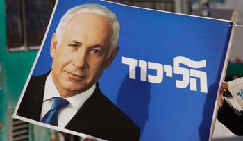 "A supporter holds an election billboard showing Israel's Likud Party leader Benjamin Netanyahu with Hebrew writing that reads ""Likud"", in Jerusalem, Friday, Feb. 6, 2009."