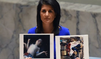 U.S. Ambassador to the UN Nikki Haley holds photos of victims of a Syrian chemical attack as she speaks at the UN on April 5, 2017.