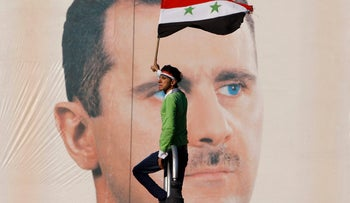FILE - A pro-Syrian regime protester waves a Syrian flag as he stands in front of portrait of Syrian President Bashar Assad, during a protest against sanctions, Damascus, Syria, in this Dec. 2, 2011 file photo.