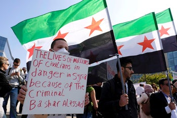 A protester holding an anti-Assad placard during a demonstration in Brussels, April 8, 2017.