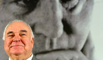 """Former German Chancellor Helmut Kohl sits in front of a large photograph of himself during a news conference to promote his new book """"Erinnerungen 1982-1990"""" (Memories 1982-1990) in Berlin November 2, 2005"""