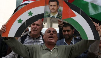 A Palestinian supporter of the Palestine Liberation Organisation (PLO) holds a banner bearing the colours of the Palestinian and Syrian flags alongsinde a portrait of the Syrian president as they demonstrate in the centre of the West Bank city of Nablus against US air strikes on Syria.