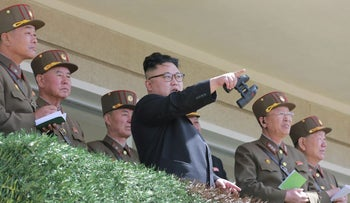 In this undated photo distributed on Friday, April 14, 2017, by the North Korean government, North Korean leader Kim Jong Un watches a military drill at an undisclosed location.