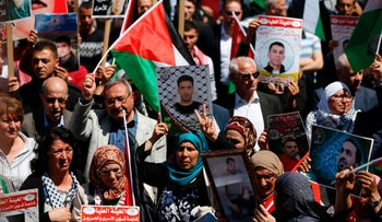 Protesters hold portraits of Palestinian prisoners during a rally in the West Bank city of Ramallah to show their support to Palestinians detained in Israeli jails after hundred of them launched a hunger strike on April 17, 2017. More than 1,000 Palestinians in Israeli jails launched a hunger strike following a call from Palestinian leader and prominent prisoner Marwan Barghouti, a Palestinian Authority official said. / AFP PHOTO / ABBAS MOMANI