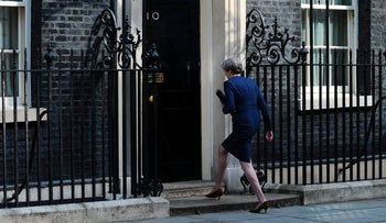British Prime Minister Theresa May walks inside 10 Downing Street after calling for an early general election on June 8, April 18, 2017.