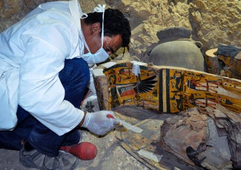 An archaeologist works on a wooden coffin discovered in a 3,500-year-old tomb in the Draa Abul Nagaa necropolis, near the southern Egyptian city of Luxor, on April 18, 2017.