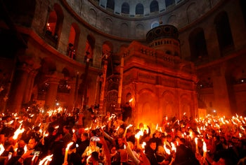 """Christian Orthodox worshipers hold up candles during the ceremony of the """"Holy Fire"""" in the Church of the Holy Sepulchre in Jerusalem's Old City, on April 15, 2017."""