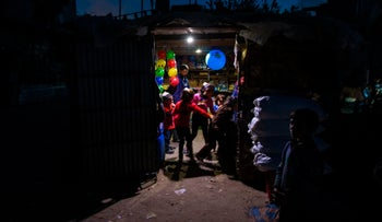 Palestinian children stand at the entrance of a shop lit up using a generator  during a power cut in a poor neighbourhood of Beit Lahia, in the northern Gaza Strip, on April 17, 2017.