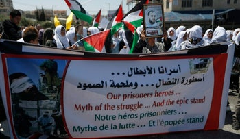 People hold banners during a rally in support of Palestinian prisoners in Bethlehem, April 17, 2017.