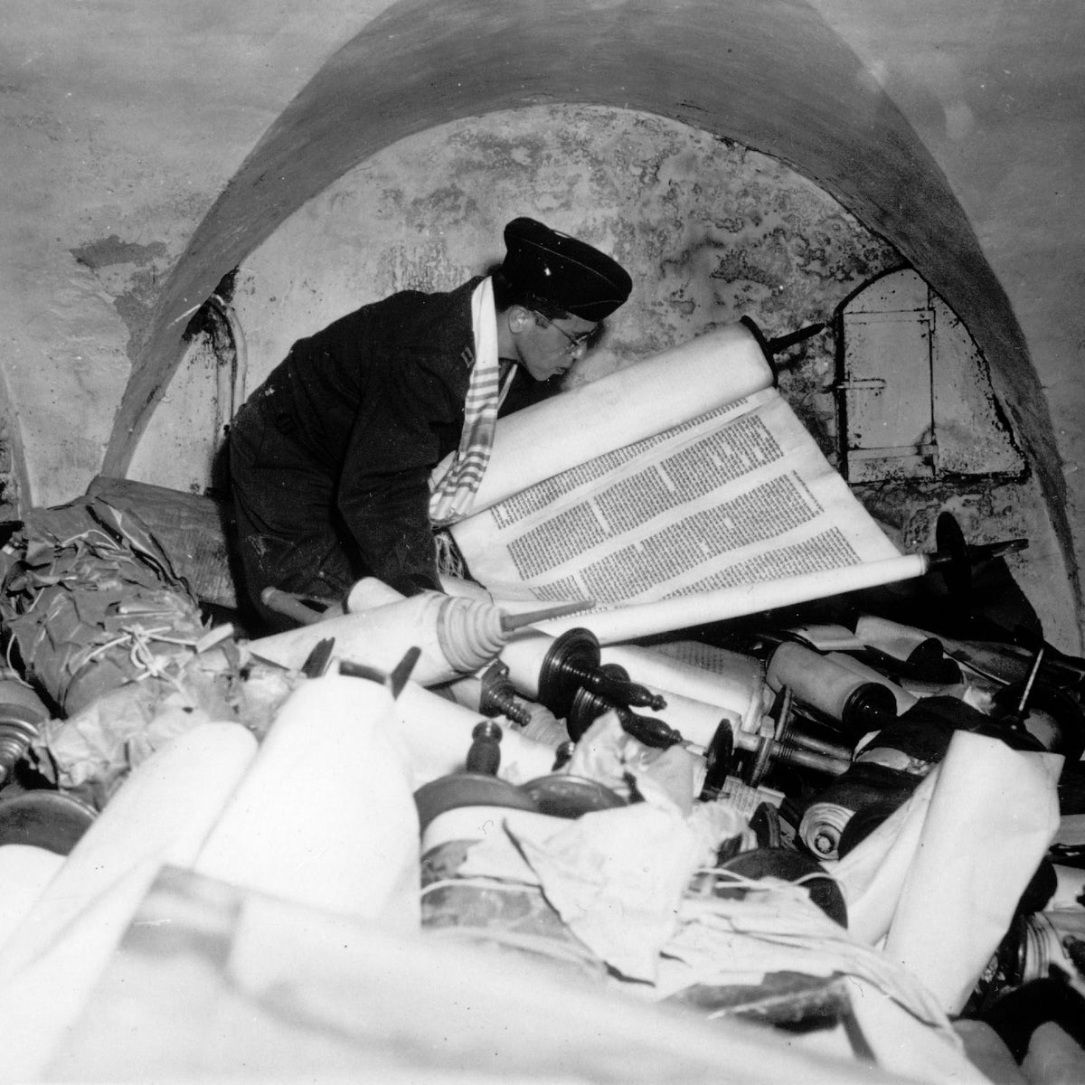 Chaplain Samuel Blinder examines Torah scrolls looted by the Nazis and hidden in a basement in Frankfurt, 1945.