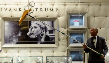 (FILES) This file photo taken on January 17, 2017 shows a worker cleaning the windows of the Ivanka Trump Boutique at Trump Tower in New York.