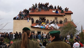 Pro-settlement activists gather in a house in the settlement of Ofra during an operation by Israeli forces to demolish nine homes there, February 28, 2017.