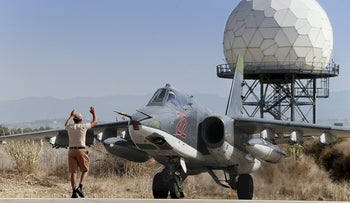 A Russian ground staff member signals to the pilot of a Sukhoi Su-25 fighter jet at the Khmeimim airbase near Latakia, Syria, October 2015.