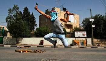 A Palestinian protester uses a slingshot to hurl stones towards Israeli security forces during clashes following a demonstration in the West Bank town of Bethlehem on April 21, 2017.